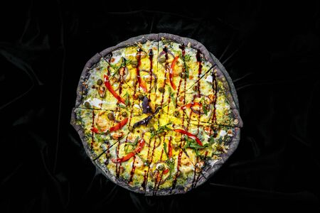 Tasty pizza on black background. Top view of hot pizza.