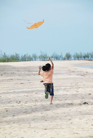 a girl is playing a kite along sea beach.      photo