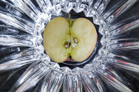 sectioned: Apple sectioned in half with seeds exposed on abstract background