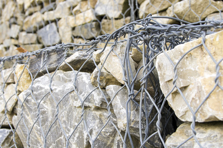 gabion: retaining drywall, built of stone filling a container made from a wire mesh hexagonal mesh, said gabion Stock Photo