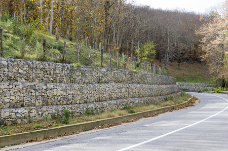 gabion mesh: retaining drywall, built of stone filling a container made from a wire mesh hexagonal mesh, said gabion Stock Photo