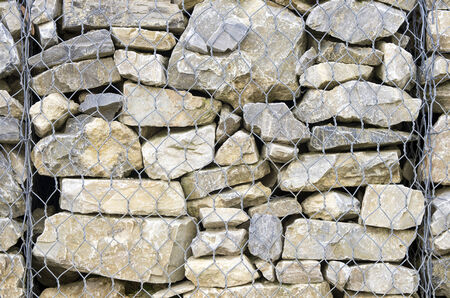retaining: retaining drywall, built of stone filling a container made from a wire mesh hexagonal mesh, said gabion Stock Photo