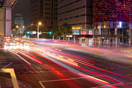 madly: Light Streaks of Cars Moving at Busy Intersection at Night Stock Photo