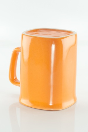 Orange ceramic cup isolated on a white background  photo