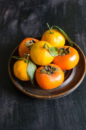 Delicious fresh persimmon and tangerine fruit on wooden plate Standard-Bild - 134147009