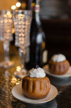 Festive meal with champagne, drinking glasses and a garland and rum baba soaked in sweet syrup stuffed with currants and cream for dessert Stock Photo