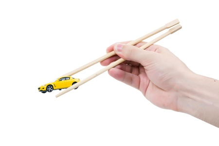 small sushi car in chopsticks on white background Stock Photo