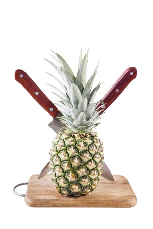 Pineapple in table with knifes on white background Stock Photo