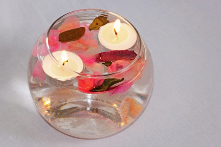 Candles and potpourri floating in bowl of water on a grey background.