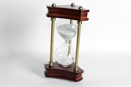An antique sandglass on a white background.