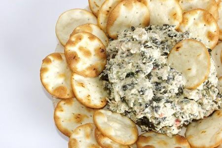 A plate with artichoke and cheese dip with pita bread chips.