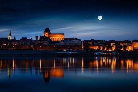 torun: Old town reflected in river at sunset. Torun, Poland.