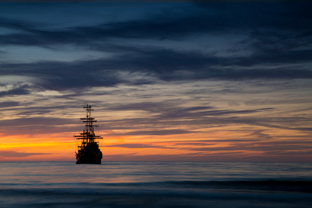 tropical sunset: Pirate ship in sunset scenery. Stock Photo