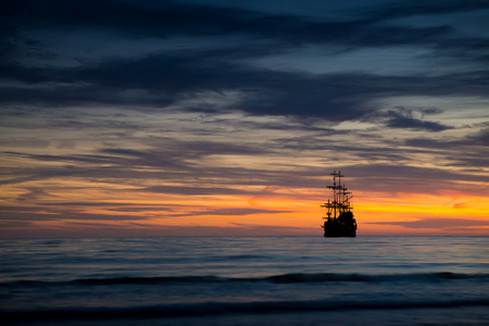 navy ship: Pirate ship in sunset scenery. Stock Photo