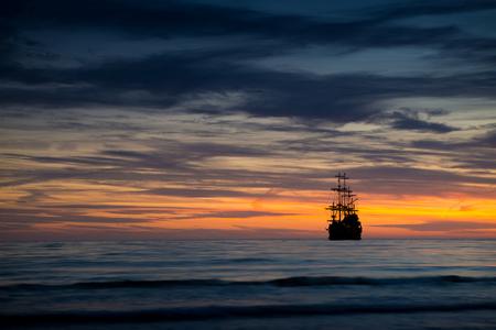 fishing scene: Pirate ship in sunset scenery. Stock Photo