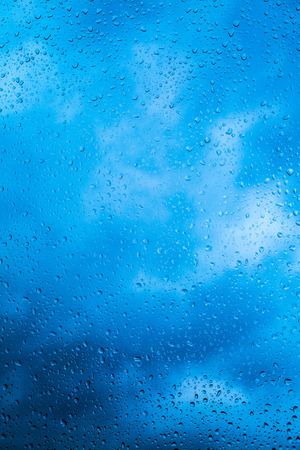 Water drops on a window glass after the rain. The sky with clouds on background.