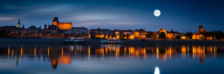 Old town reflected in river at sunset. Torun, Poland Stock Photo