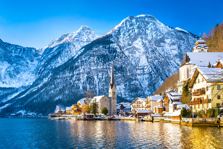 Classic postcard view of famous Hallstatt lakeside town in the Alps with traditional passenger ship on a beautiful cold sunny day with blue sky and clouds in winter, Austria Banque d'images - 124553786