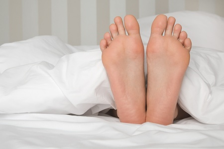 bare feet in bed Stock Photo - 12082102