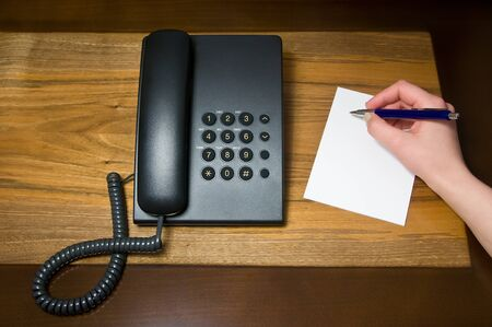 landline telephone and human hand writing note  landline telephone and human hand writing note  photo