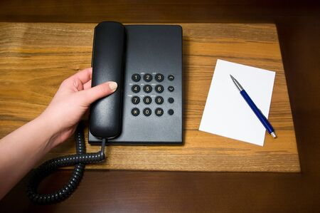 Human hand holding landline telephone receiver
