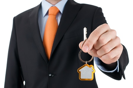 sell house: man with black suit holding a key  Stock Photo