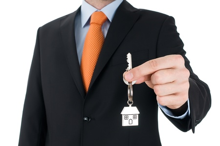 man in  black suit holding a key  photo