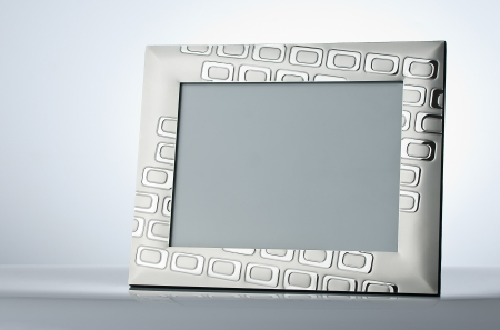 Blank silver picture frame at the table with place for your own text, photo