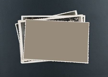 Stack of old photos on elegant black leather photo