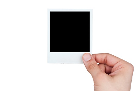 young male hand holding instant photo against white background