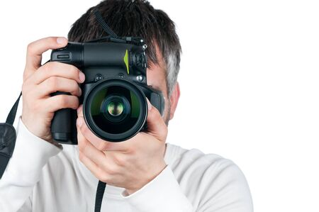 Young man with camera, isolated on white background, focus is on the lens