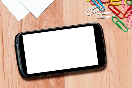 paper clips: smartphone  on a desk with clipping paths for the screen. Workplace with mobile phone, paper and clips on work table