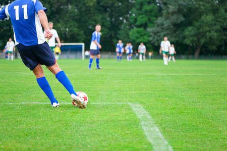 soccer match: soccer player kicks the ball. Horizontal image of soccer ball with foot of player.Soccer football field stadium grass.