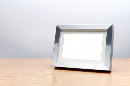 home office desk: Blank silver picture frame on the table with clipping path Stock Photo