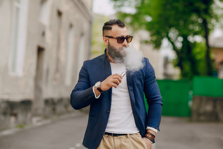 hombre con barba: hombre con barba y e-cigarrillo al aire libre Foto de archivo