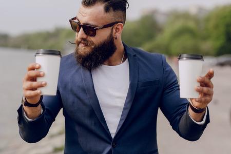 hombre barba: hombre con barba que lleva café Foto de archivo