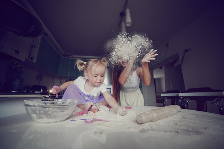 woman baking: young beautiful mother teaches daughter prepare dough in the kitchen Stock Photo