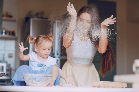 young beautiful mother teaches daughter prepare dough in the kitchen Zdjęcie Seryjne