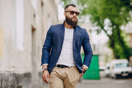 stylishly: manly bearded man dressed stylishly stands on street Stock Photo