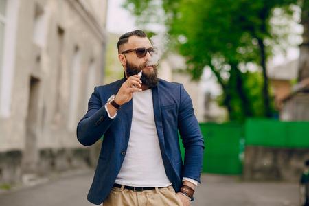 bebaarde man met e-sigaret buiten op zomerse dag Stockfoto