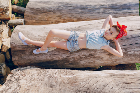 little girl sitting on the wood style pin up in jeans clothes Stock Photo