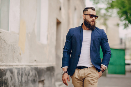 manly: manly bearded man dressed stylishly stands on street Stock Photo