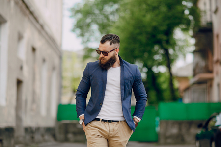 stylishly: manly bearded man dressed stylishly stands on street Stock Photo