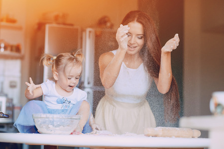 young beautiful mother teaches daughter prepare dough in the kitchen Imagens