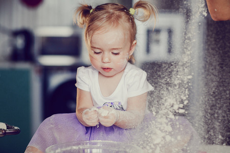 beautiful little girl learns to cook a meal in the kitchen