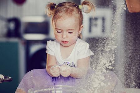 mooi klein meisje leert om een maaltijd in de keuken koken Stockfoto