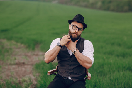 caring for: lone bearded man caring for his beard in the field
