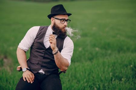 Solitario uomo barbuto gode nel campo della e-sigaretta Archivio Fotografico - 43876968