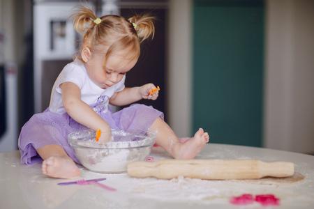 ni�as peque�as: hermosa ni�a aprende a cocinar una comida en la cocina Foto de archivo