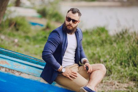 Uomo barbuto sulla barca con il giorno d'estate telefono Archivio Fotografico - 44002410